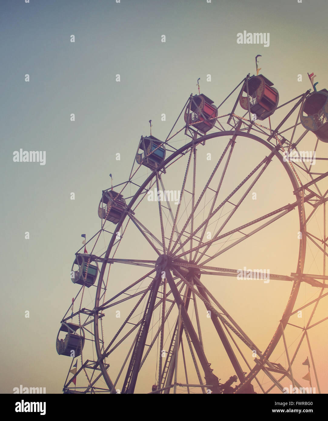 A Ferris wheel is spinning at a carnival at sunset for an artistic activity or summer memory concept. Stock Photo