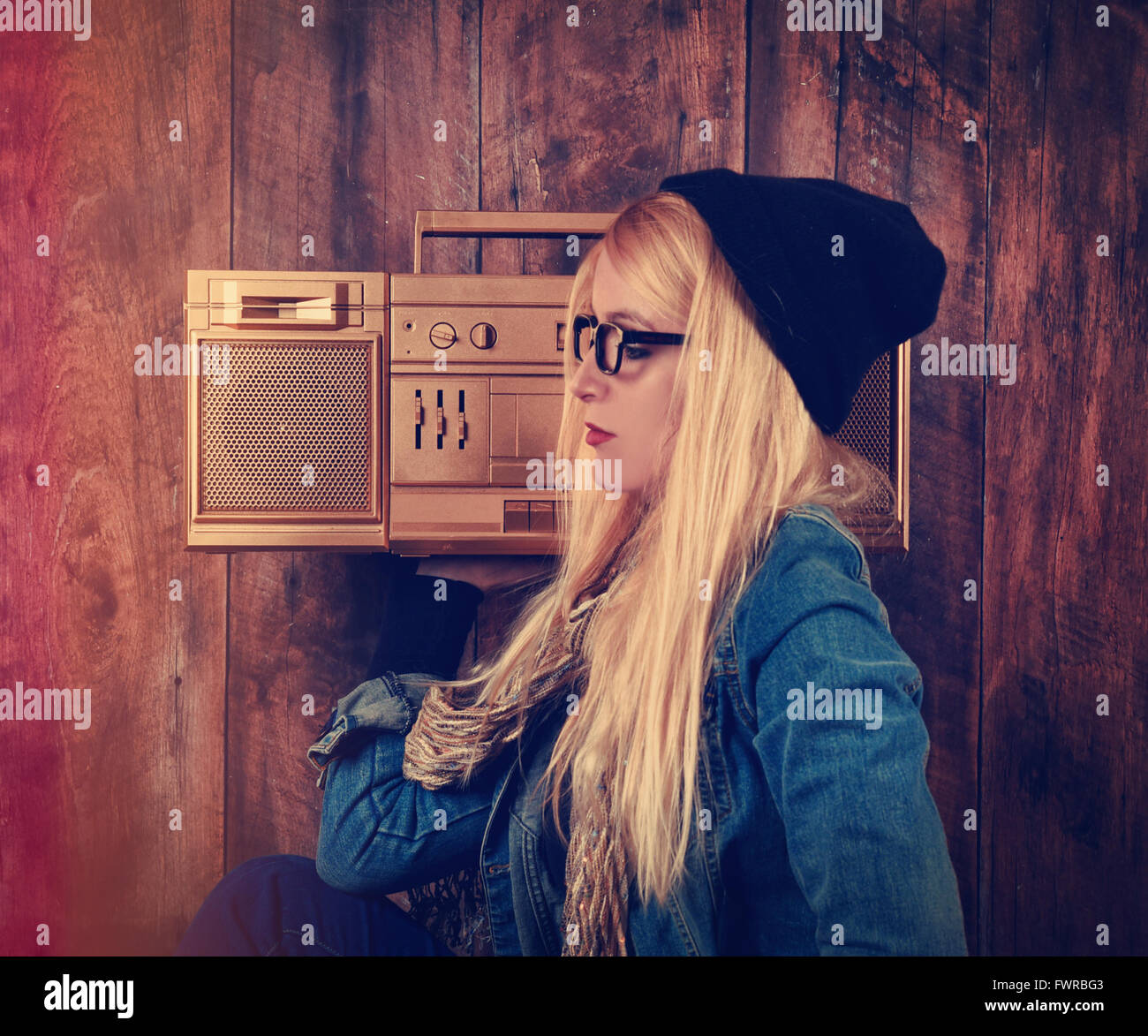 A hipster girl with glasses is listening to a vintage gold boombox radio with a speaker for a music entertainment - Stock Image