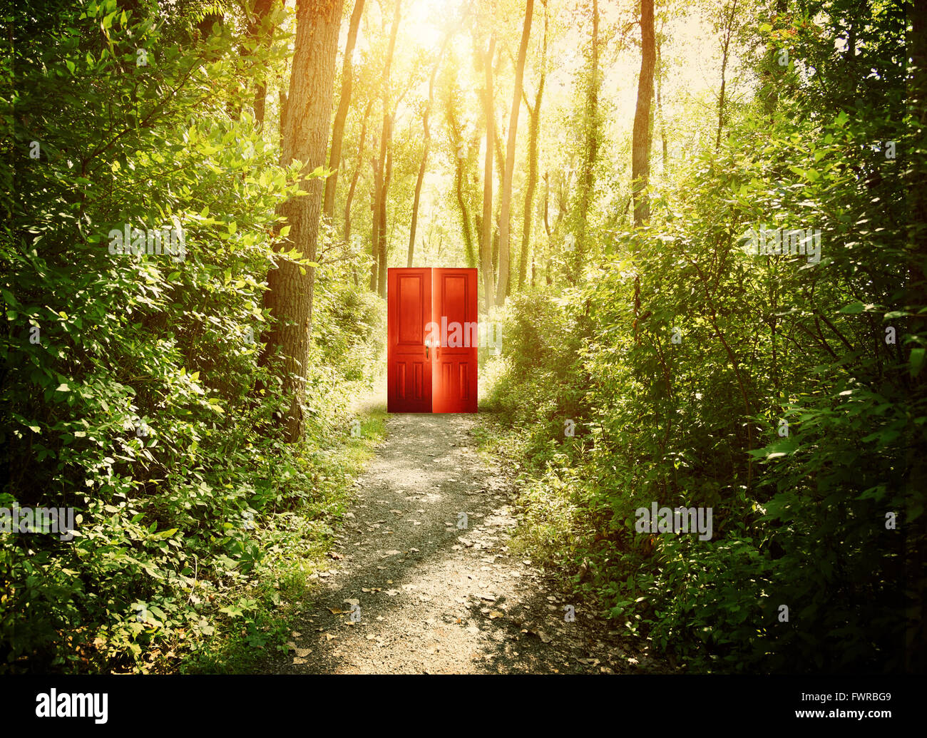 A red doorway is on a trail in the woods with trees for a conceptual concept about faith, freedom or freedom concept. - Stock Image