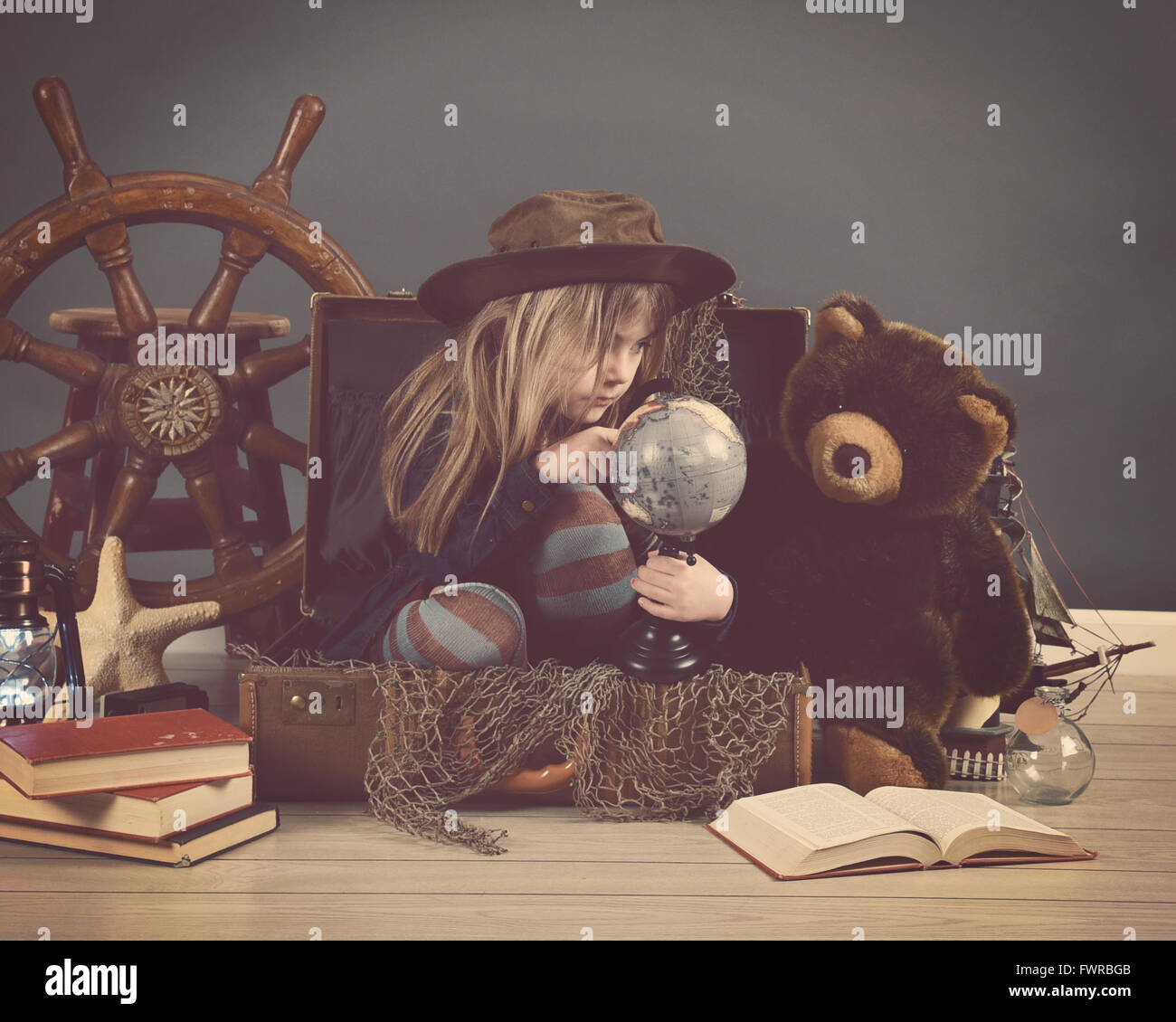 A little child is sitting in a travel suitcase looking at a globe with sea props for an imagination or education - Stock Image