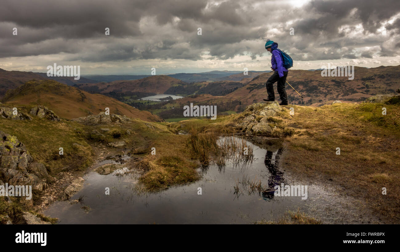 Looking towards Grasmere from Gibson's Knott with female walker on path, The Lake District, England - Stock Image