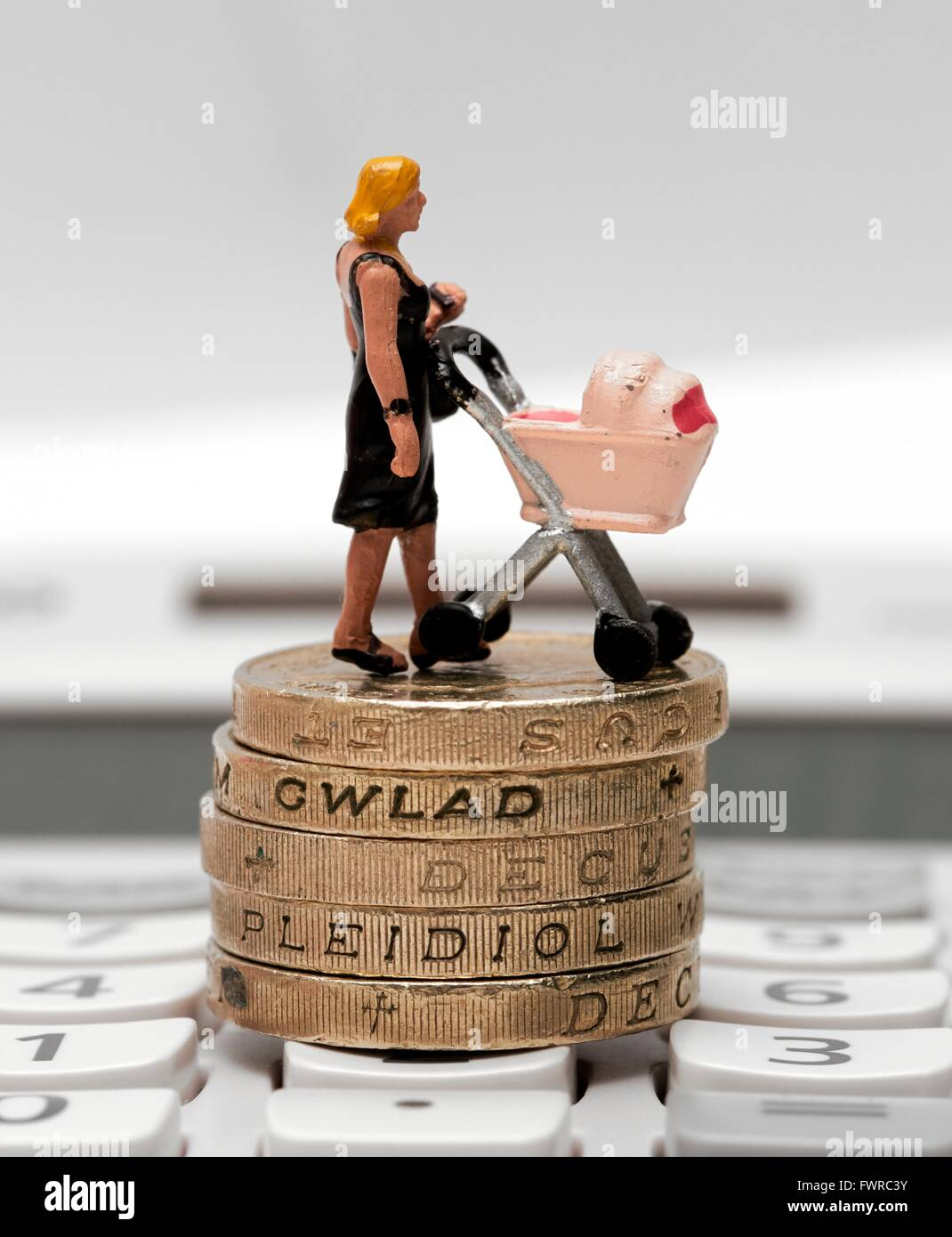 A miniature figurine woman with a pram standing on top of one pound coins - Stock Image