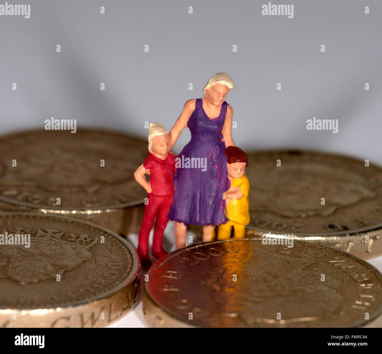 A miniature figurine woman with 2 children standing in between one pound coins - Stock Image