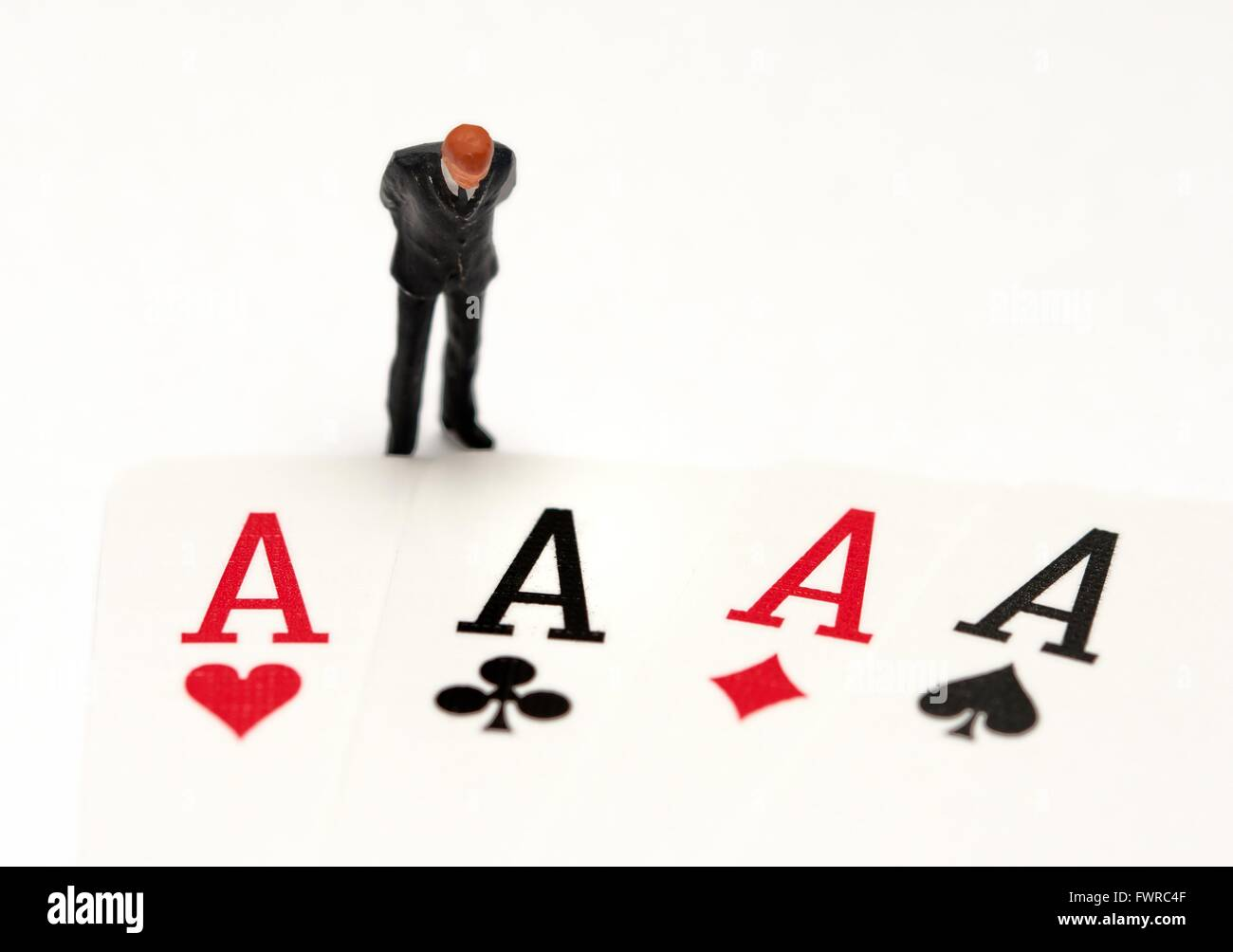 A miniature figurine business man looking down at 4 aces from a deck of playing cards - Stock Image