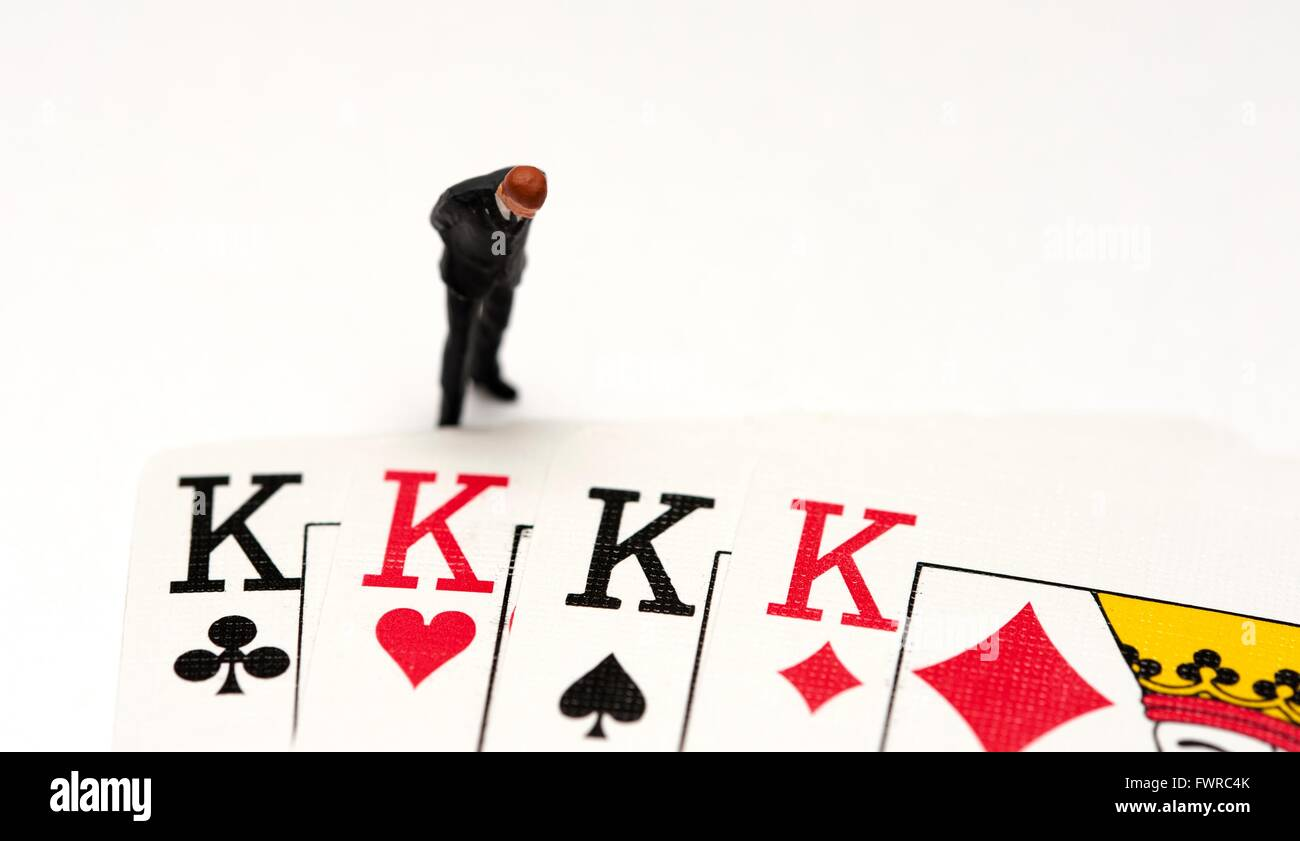 A miniature figurine business man looking down at 4 kings from a deck of playing cards - Stock Image