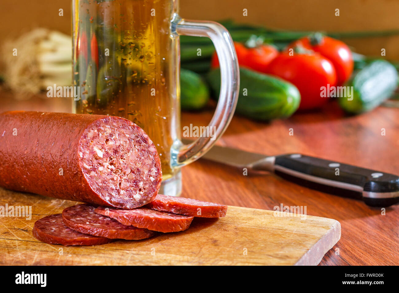 Sujuk sausage on wooden cutting board with beer mug, knife and fresh vegetables in background. Copy space Stock Photo