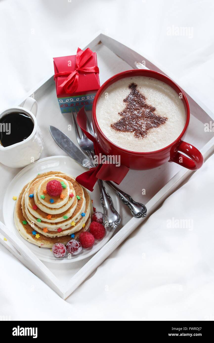 Christmas Breakfast on a tray pancakes and Coffee with chocolate dusting - Stock Image