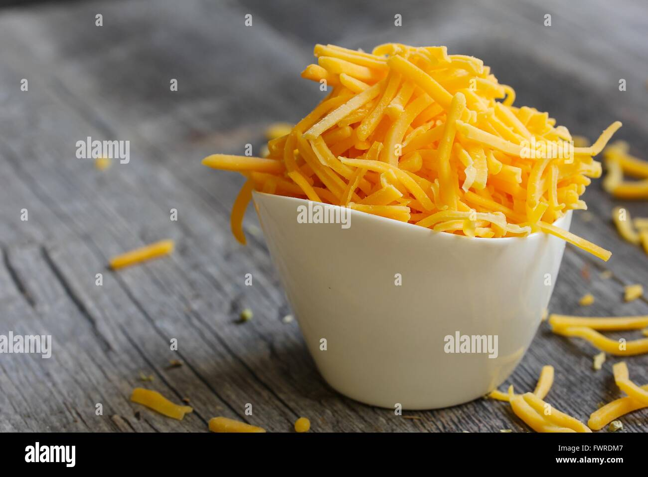 Shredded cheddar cheese in white cup  close up - Stock Image