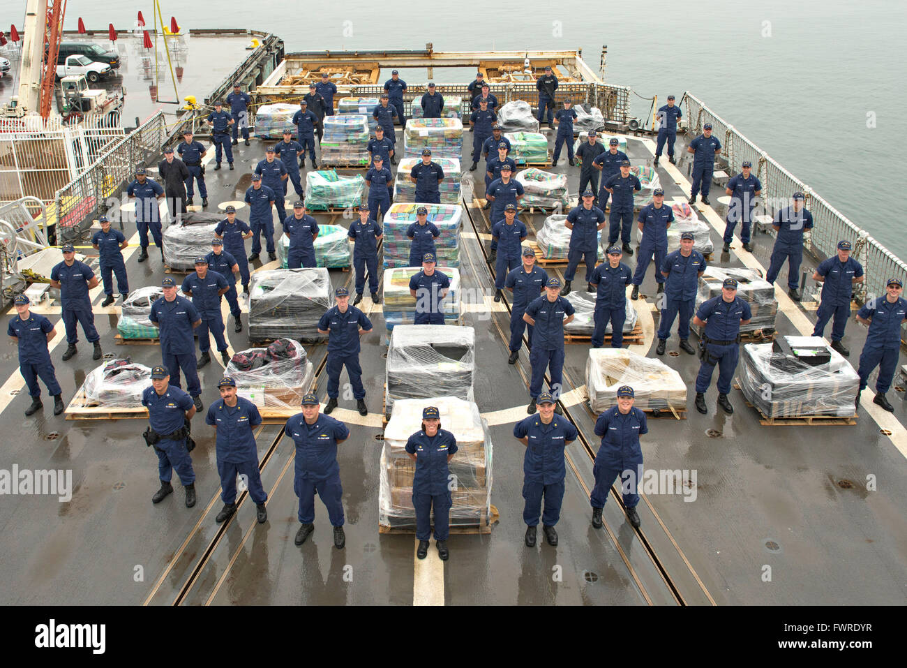 U.S. Coast Guard Cutter Bertholf crew members offload 14 tons of cocaine intercepted during the first quarter of Stock Photo