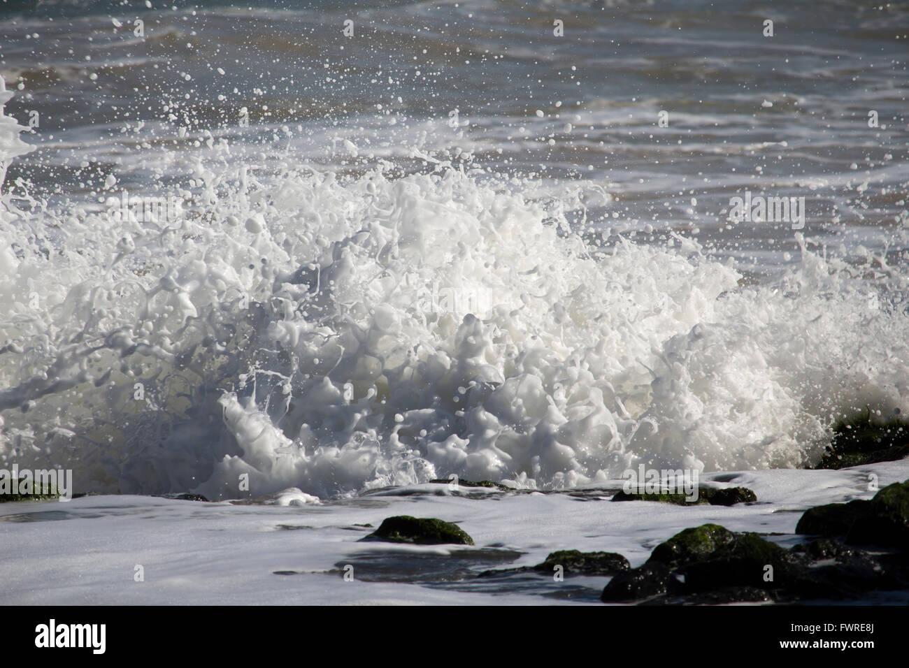 Indian Ocean waves breaking on  basalt rocks   at  Ocean Beach Bunbury Western Australia send muddy spray high into Stock Photo