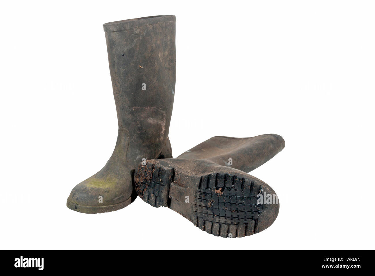 Isolated pair of grubby wellington boots showing pattern tread on sole - Stock Image