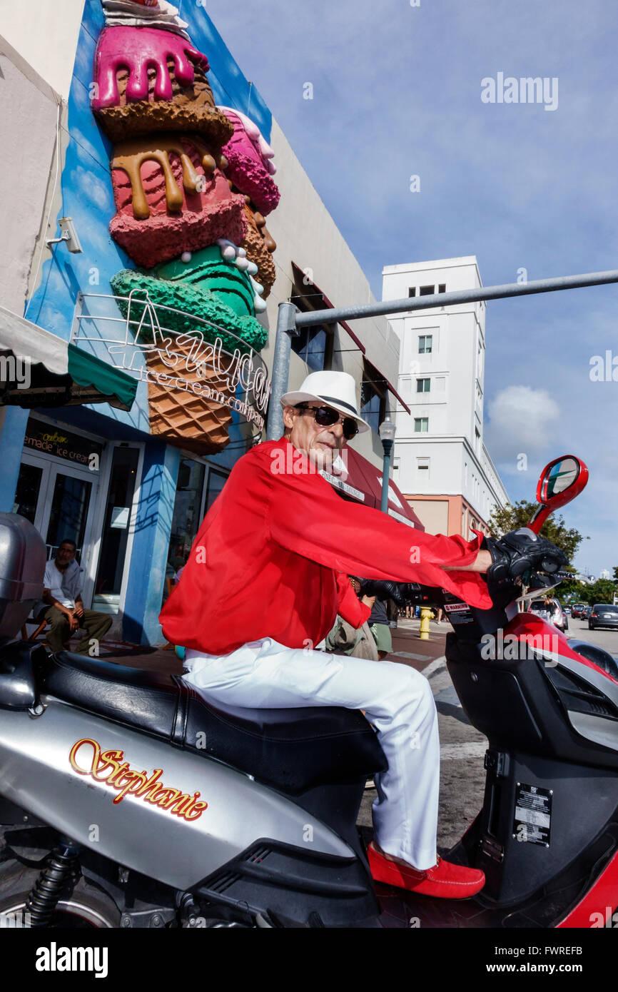 Florida FL Miami Little Havana Calle Ocho Hispanic man motor scooter hat fedora Azucar Ice Cream Company - Stock Image