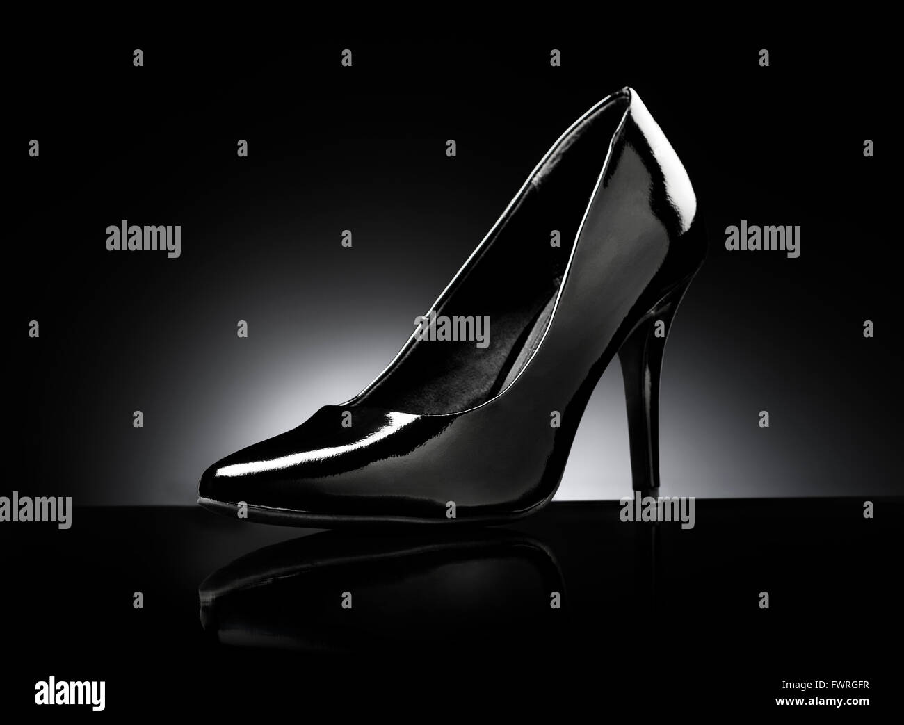 Black glossy ladies stiletto heel pump on black reflective background. - Stock Image