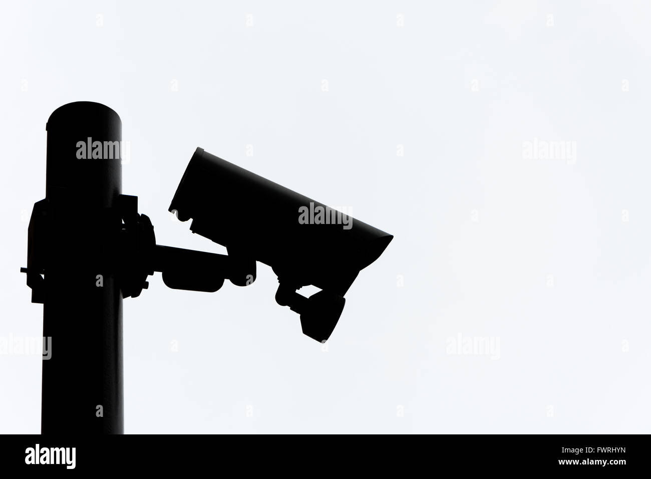 Silhouette of a CCTV camera on a pole. - Stock Image