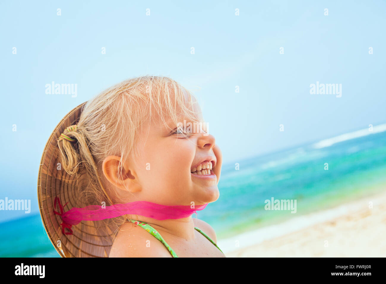 On sunny white sand beach happy smiling baby girl with vietnamese straw hat on head has fun before swimming in sea Stock Photo