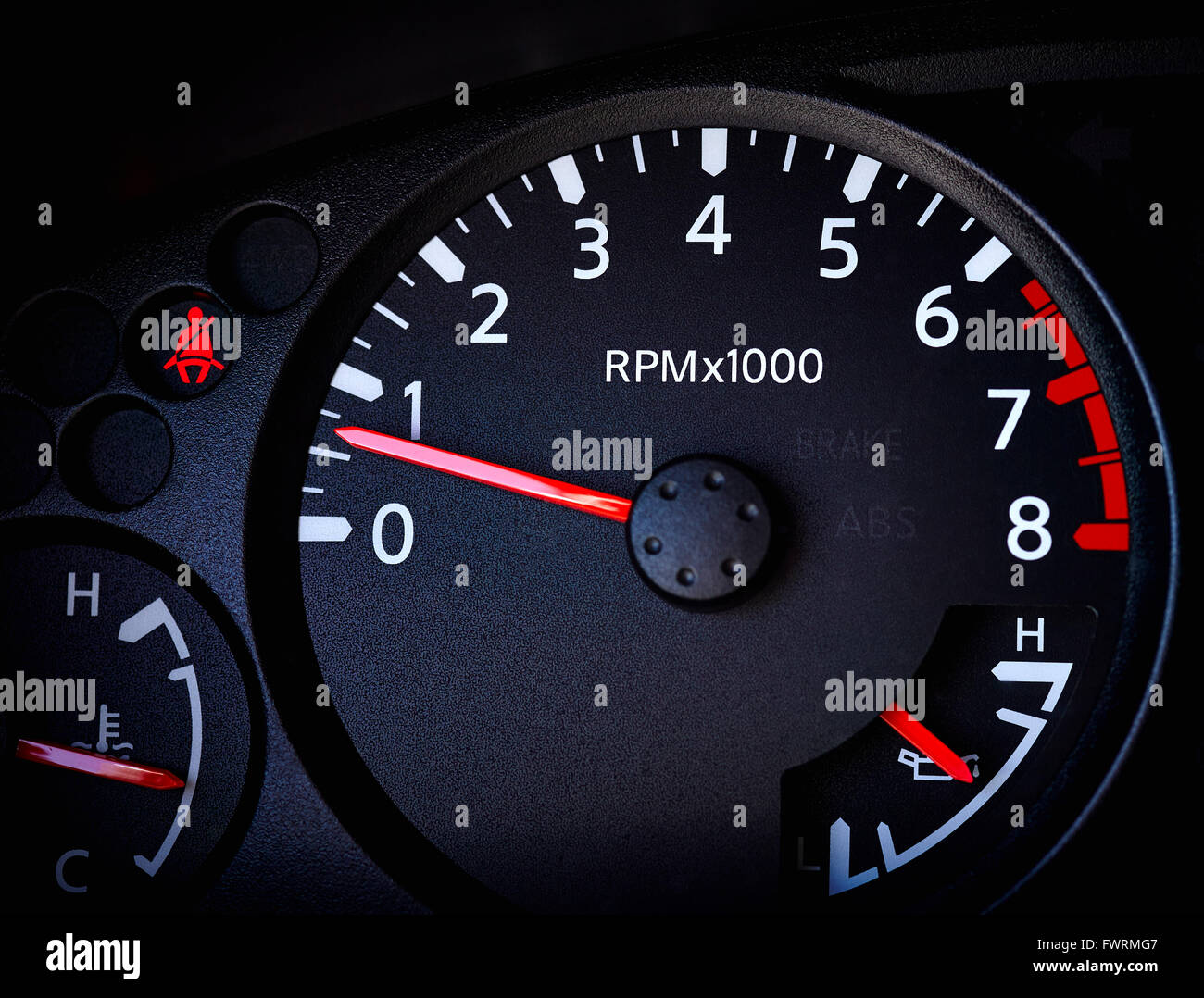 Close of up car tachometer with temperature guage, battery guage and seat belt warning light - Stock Image