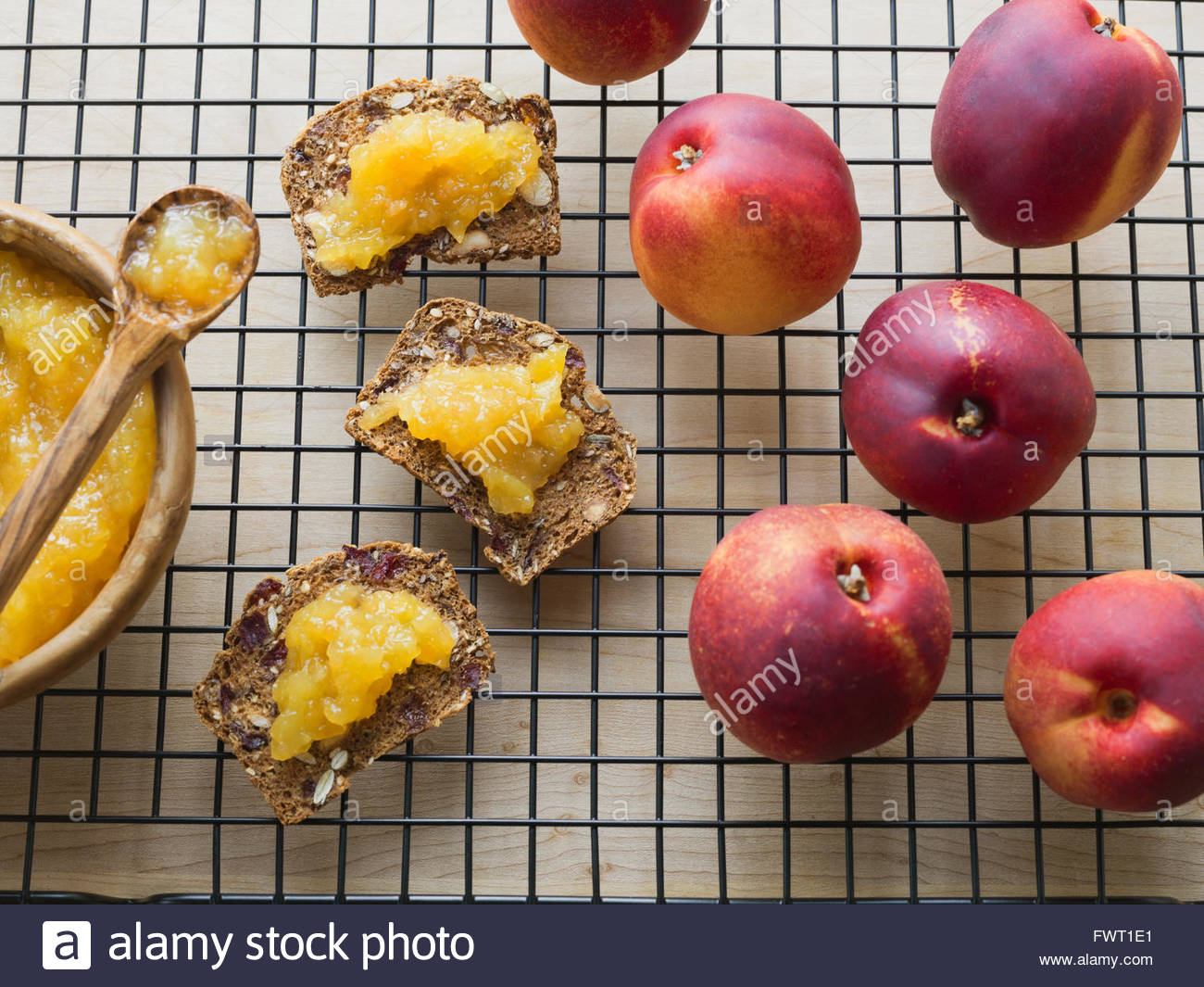 Fresh peaches and peach spread on almond crisps - Stock Image