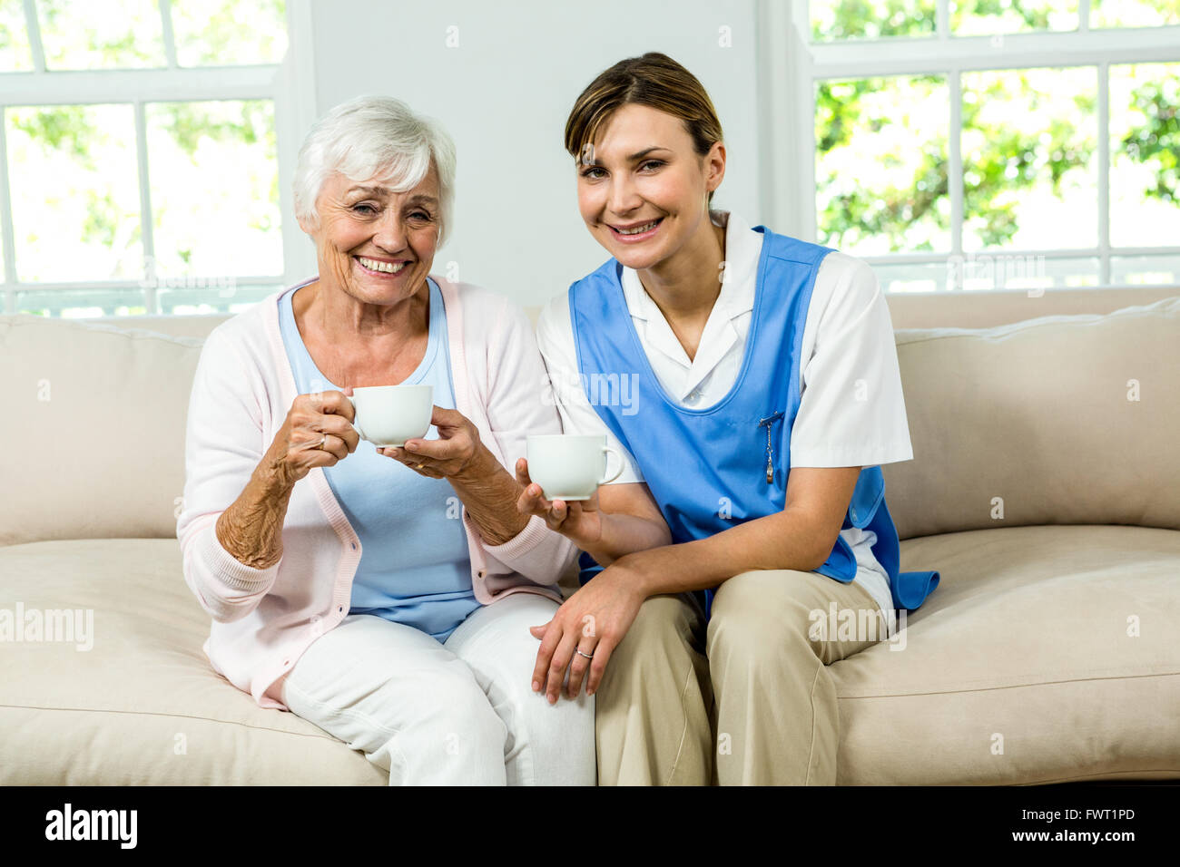 Portrait of smiling nurse with senior woman - Stock Image