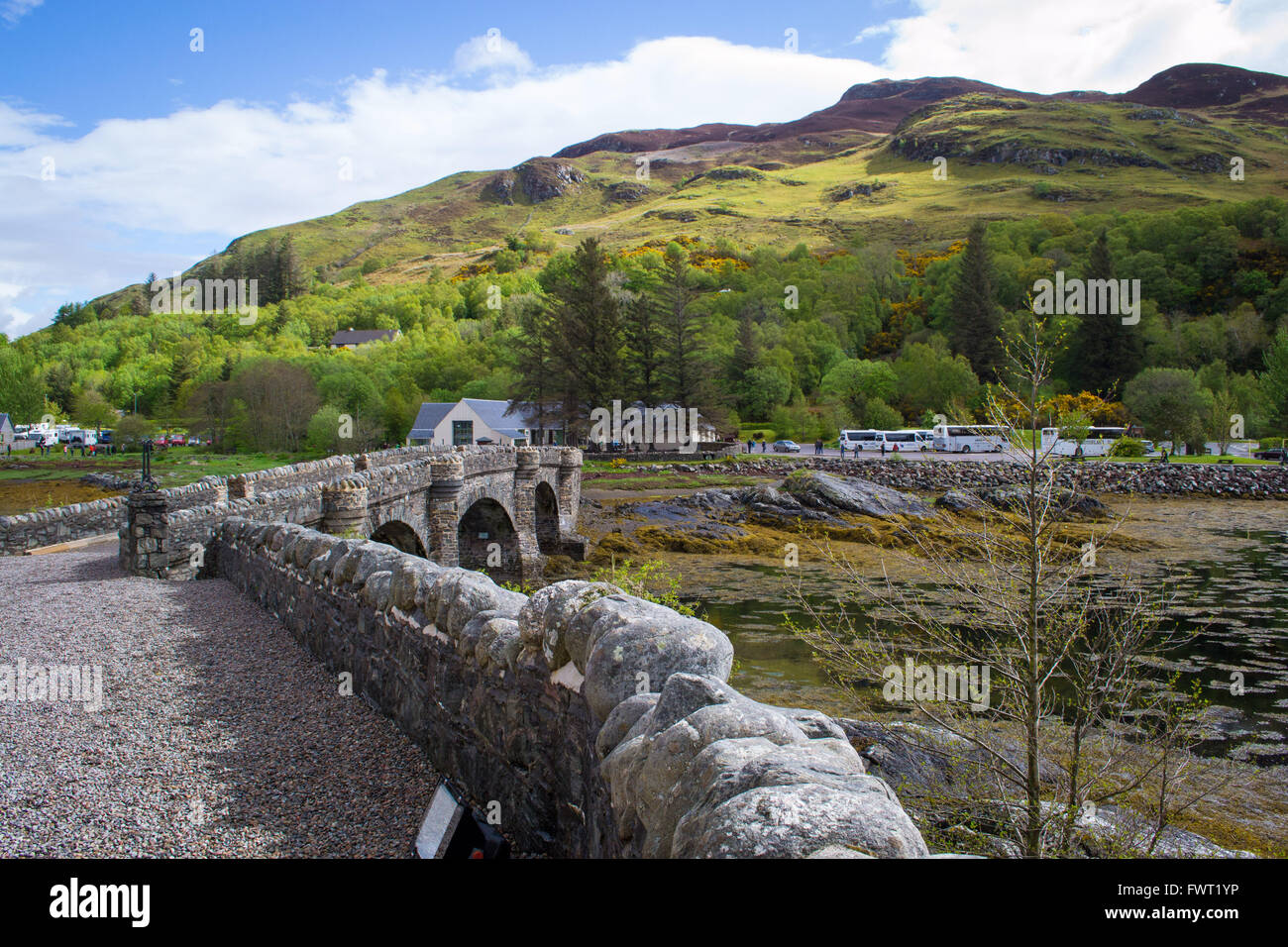 A view from Eilean Donan Castle across the bridge towards the visitor centre. - Stock Image