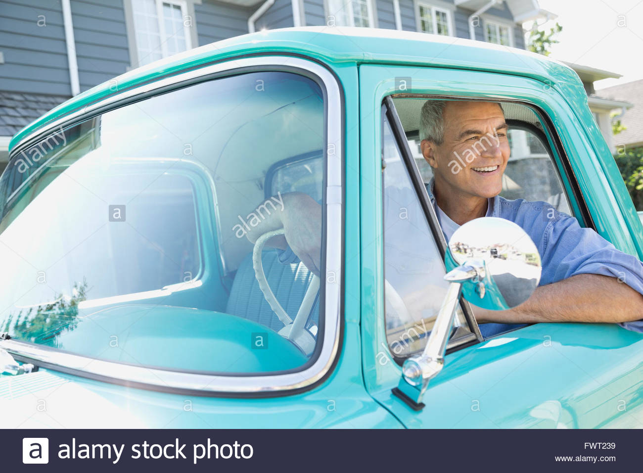Mature man looking out of window while sitting pick-up truck - Stock Image
