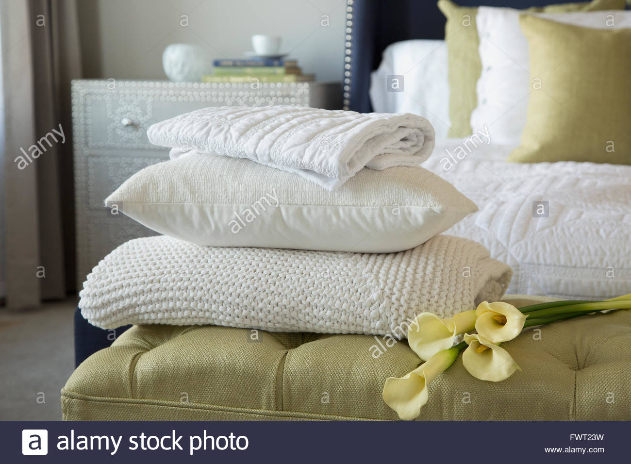 Pillow, blankets and lilies on footstool in bedroom - Stock Image
