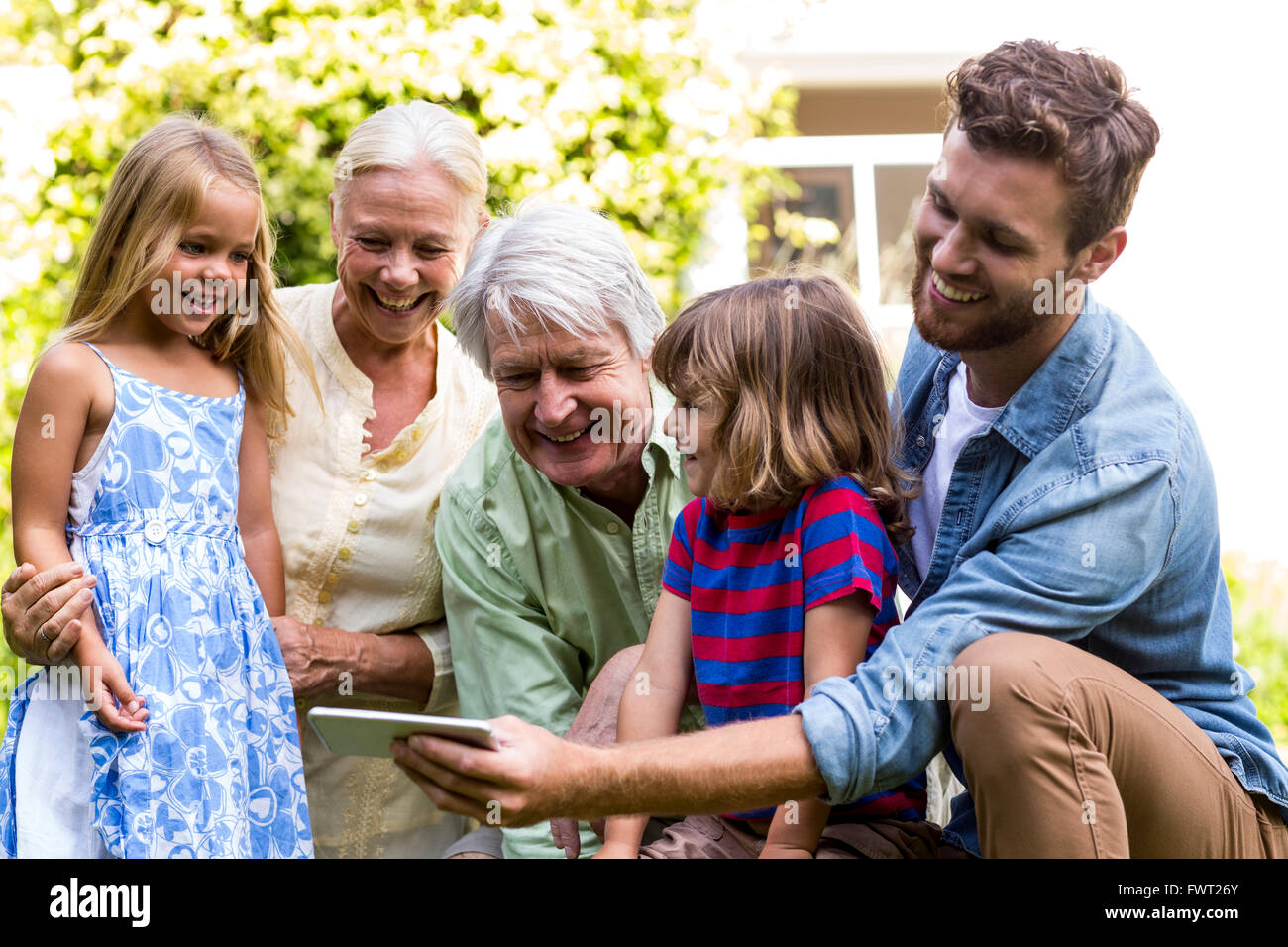 Smiling father taking selfie with family - Stock Image