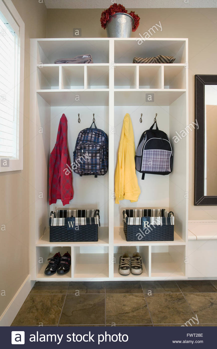 Open shelved closet with backpacks and baskets - Stock Image
