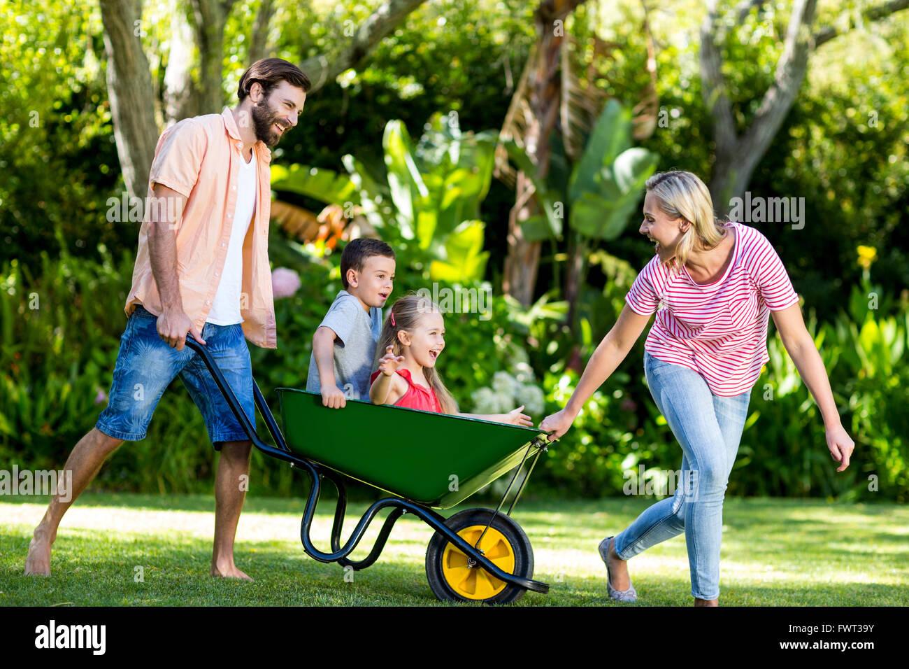 Parents pushing children sitting in wheelbarrow at yard Stock Photo