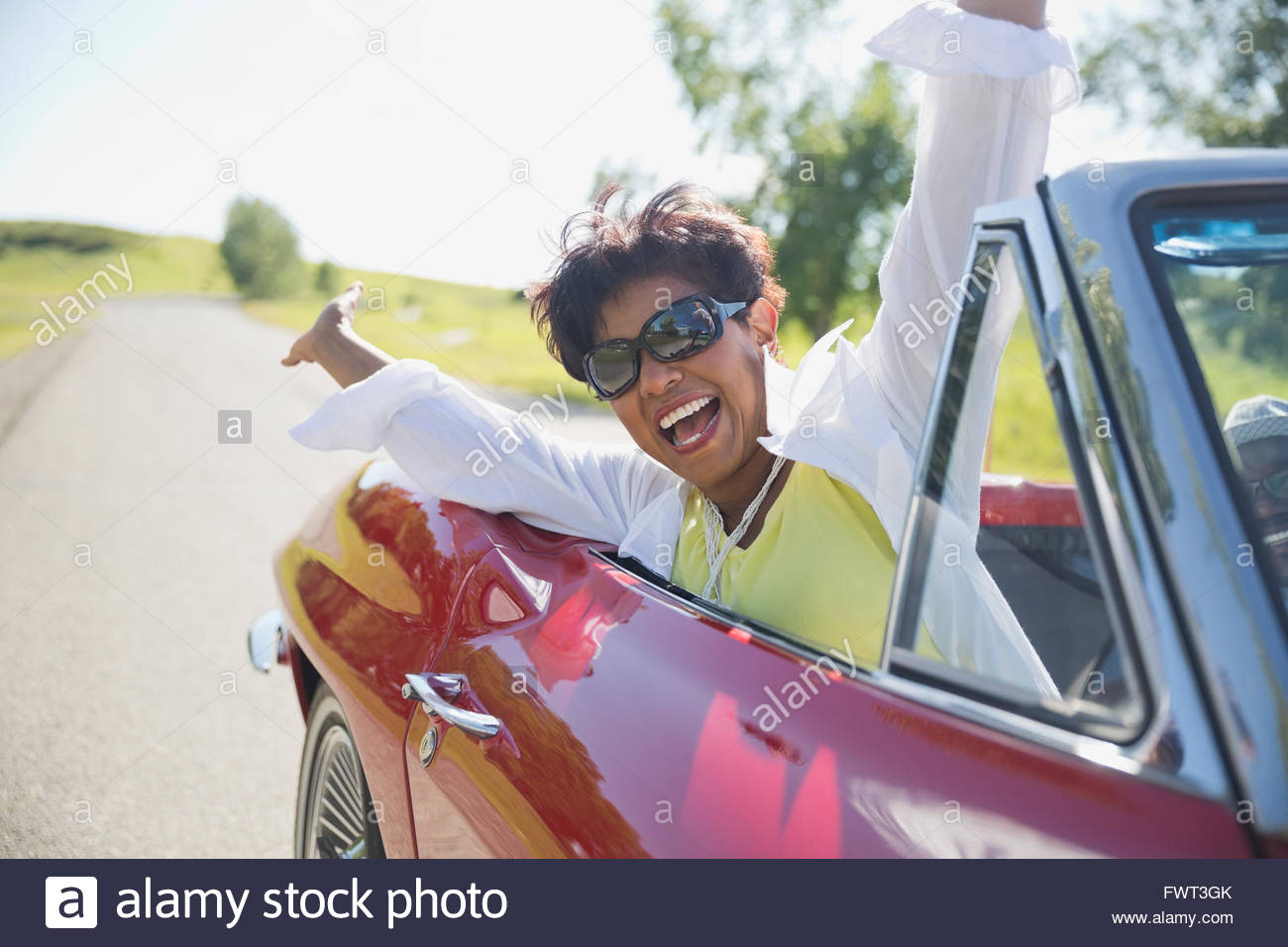 Portrait of excited middle-aged woman in red convertible - Stock Image