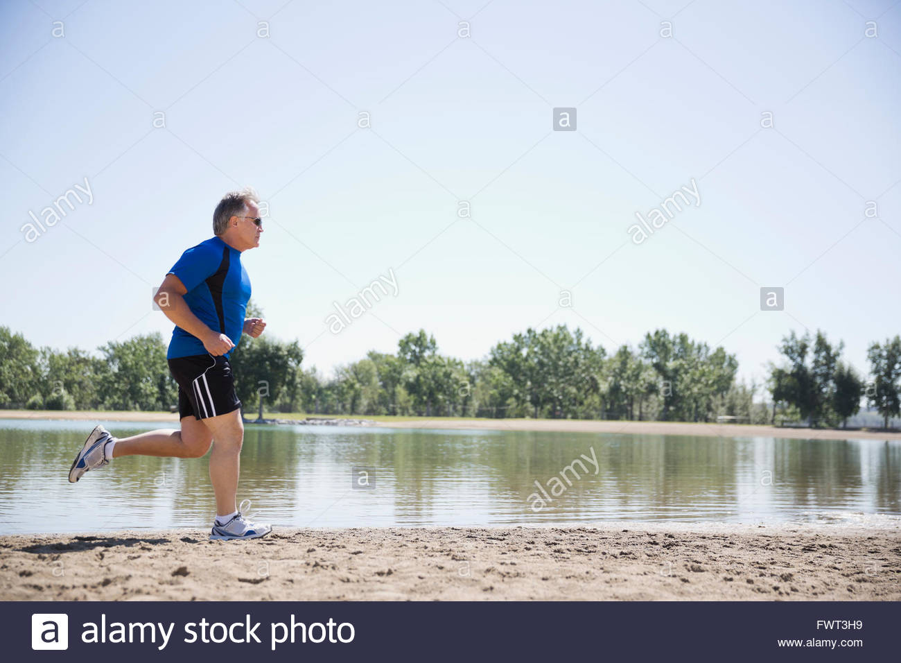 Profile shot of middle-aged man jogging on beach - Stock Image