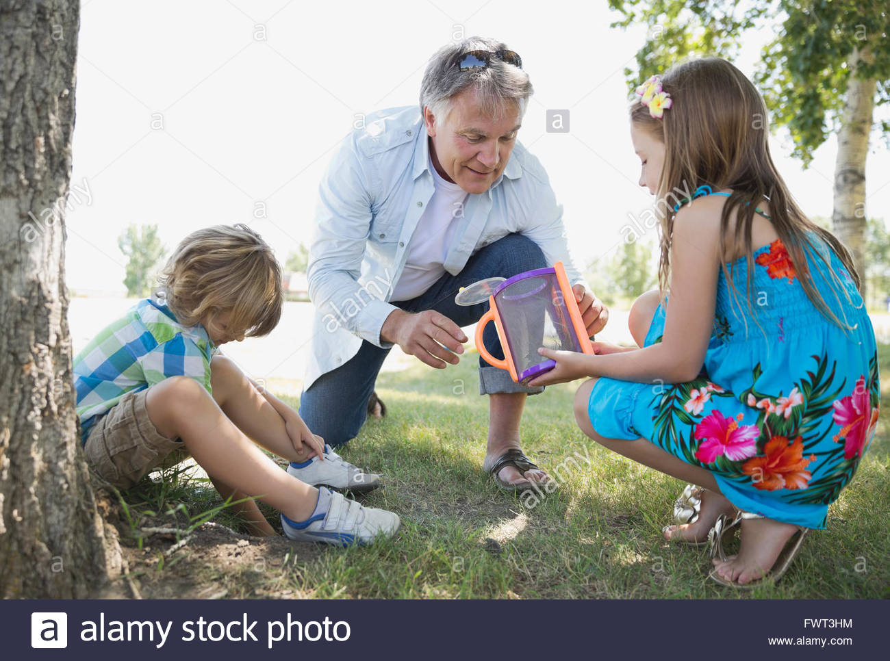 Grandfather and girl looking at insect in container - Stock Image