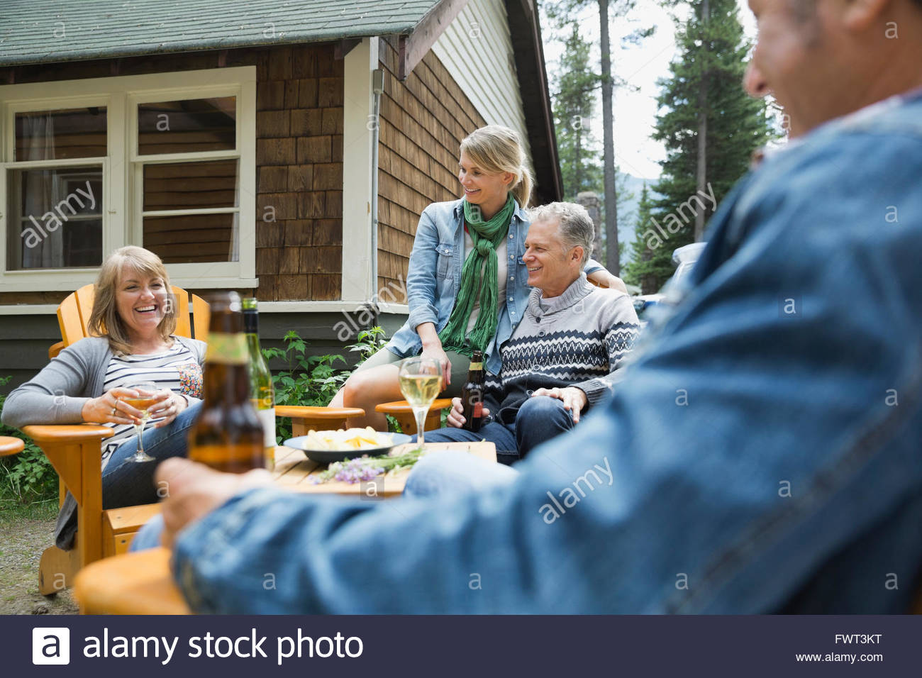 Middle-aged friends socializing outdoors - Stock Image