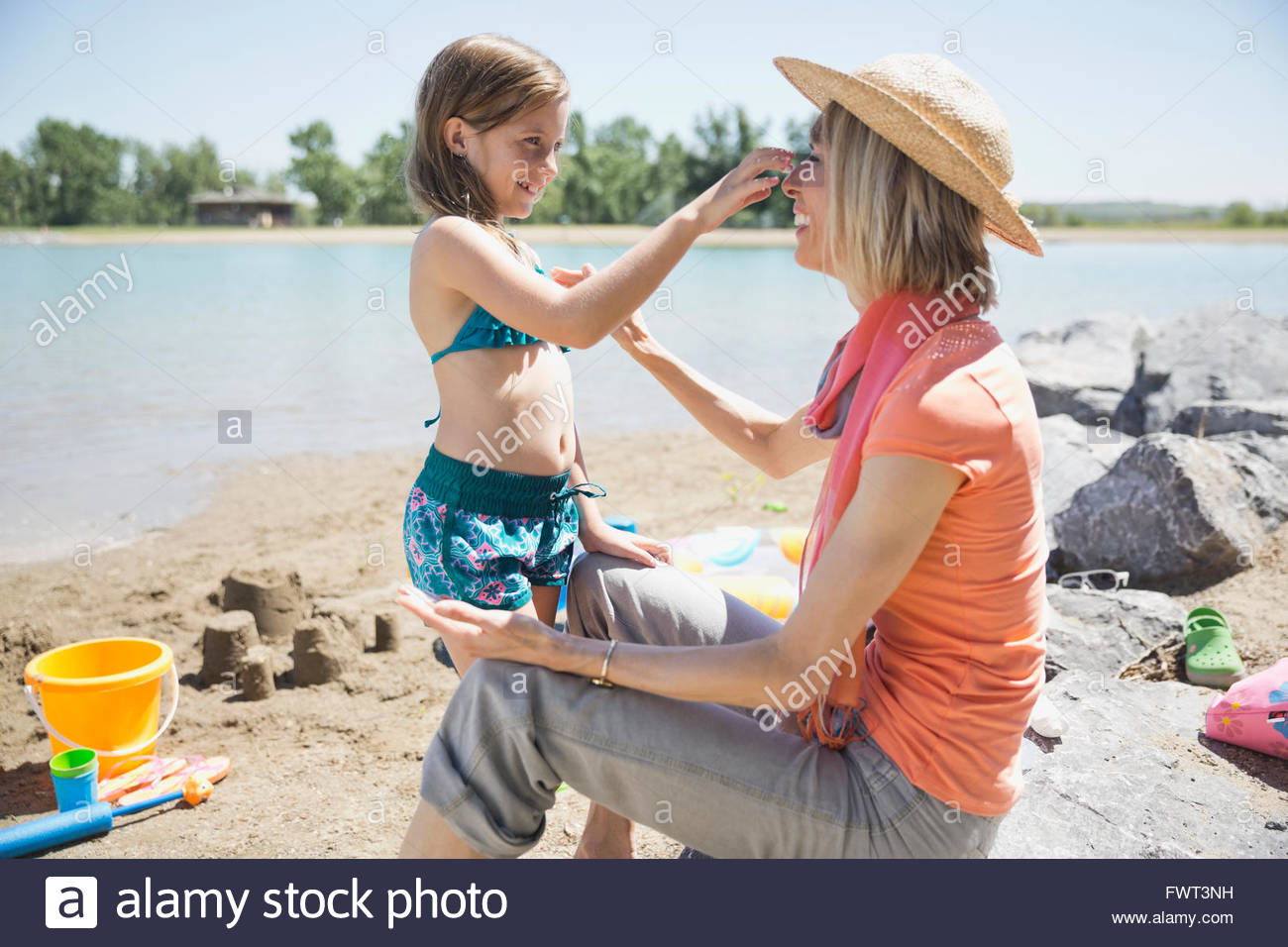 Grandmother and granddaughter applying sunscreen on each other - Stock Image