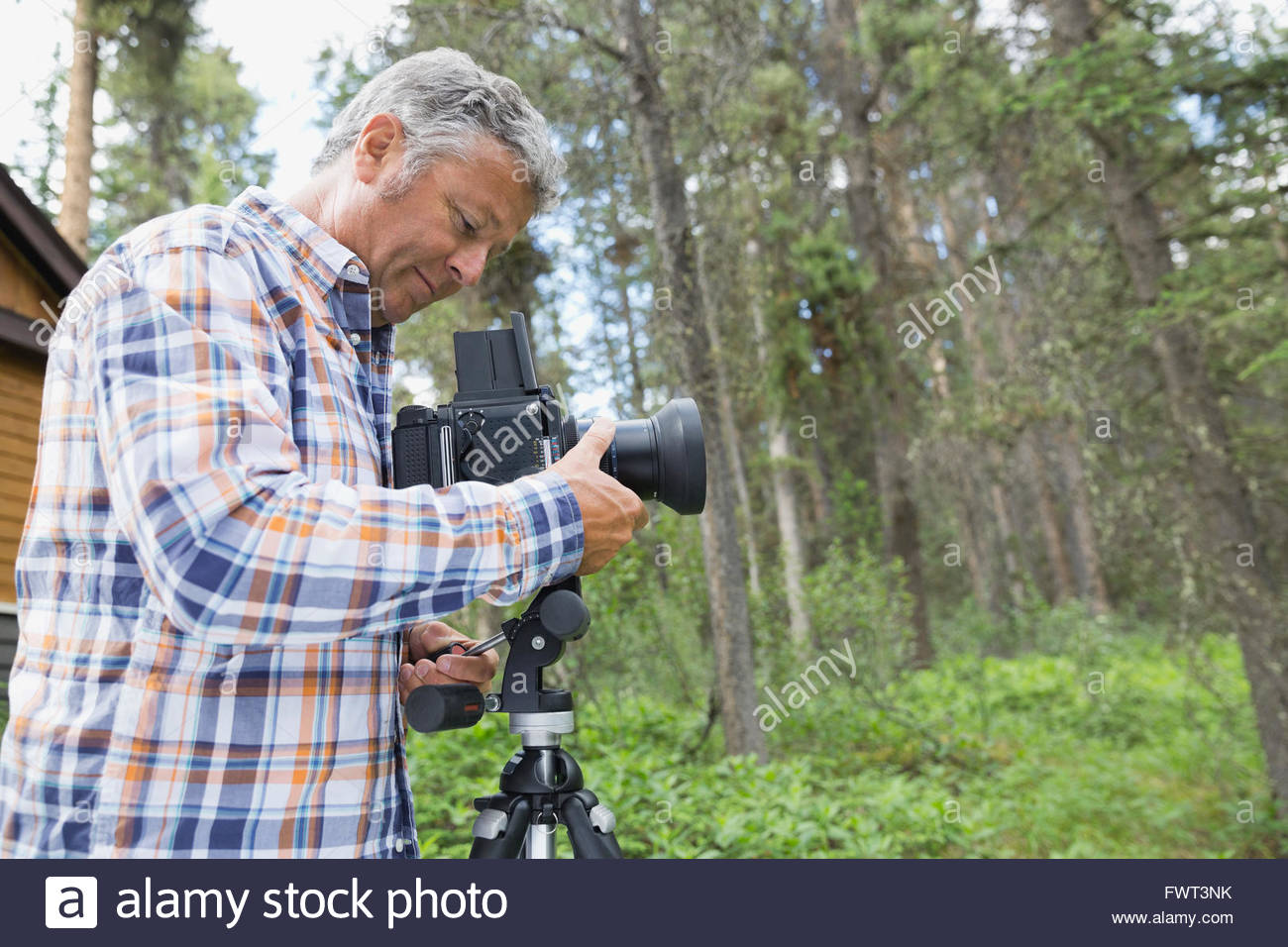 Man adjusting lens of SLR camera in yard Stock Photo