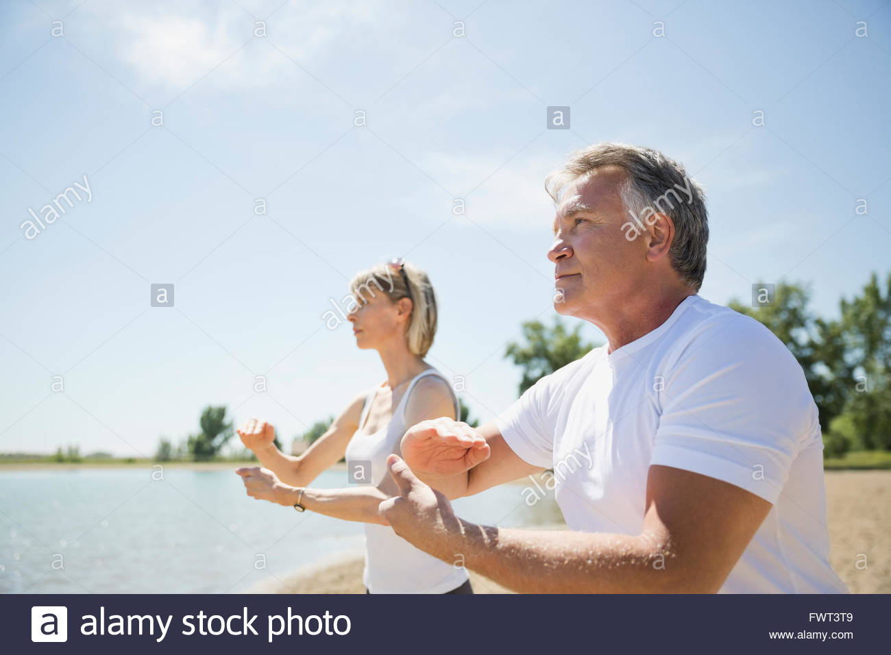 Middle-aged couple performing tai chi on beach - Stock Image