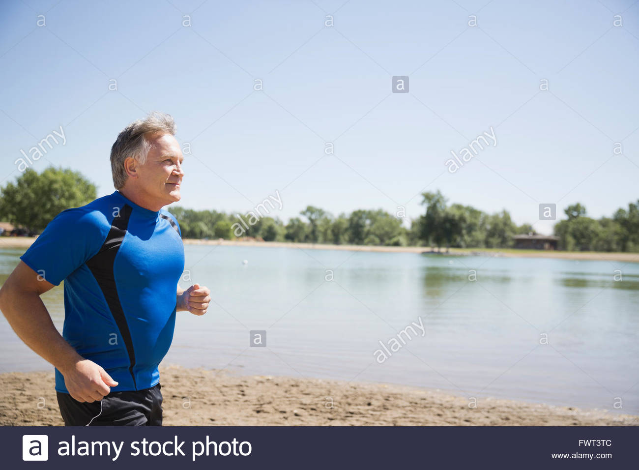 Middle-aged man jogging on beach - Stock Image