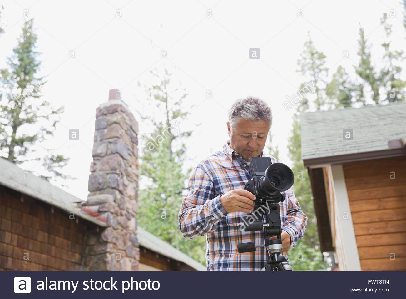 Middle-aged man adjusting lens of SLR camera in yard - Stock Image