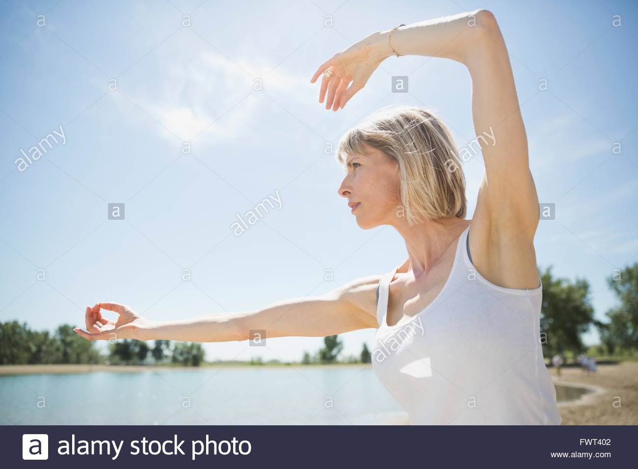Middle-aged woman performing tai chi on beach - Stock Image
