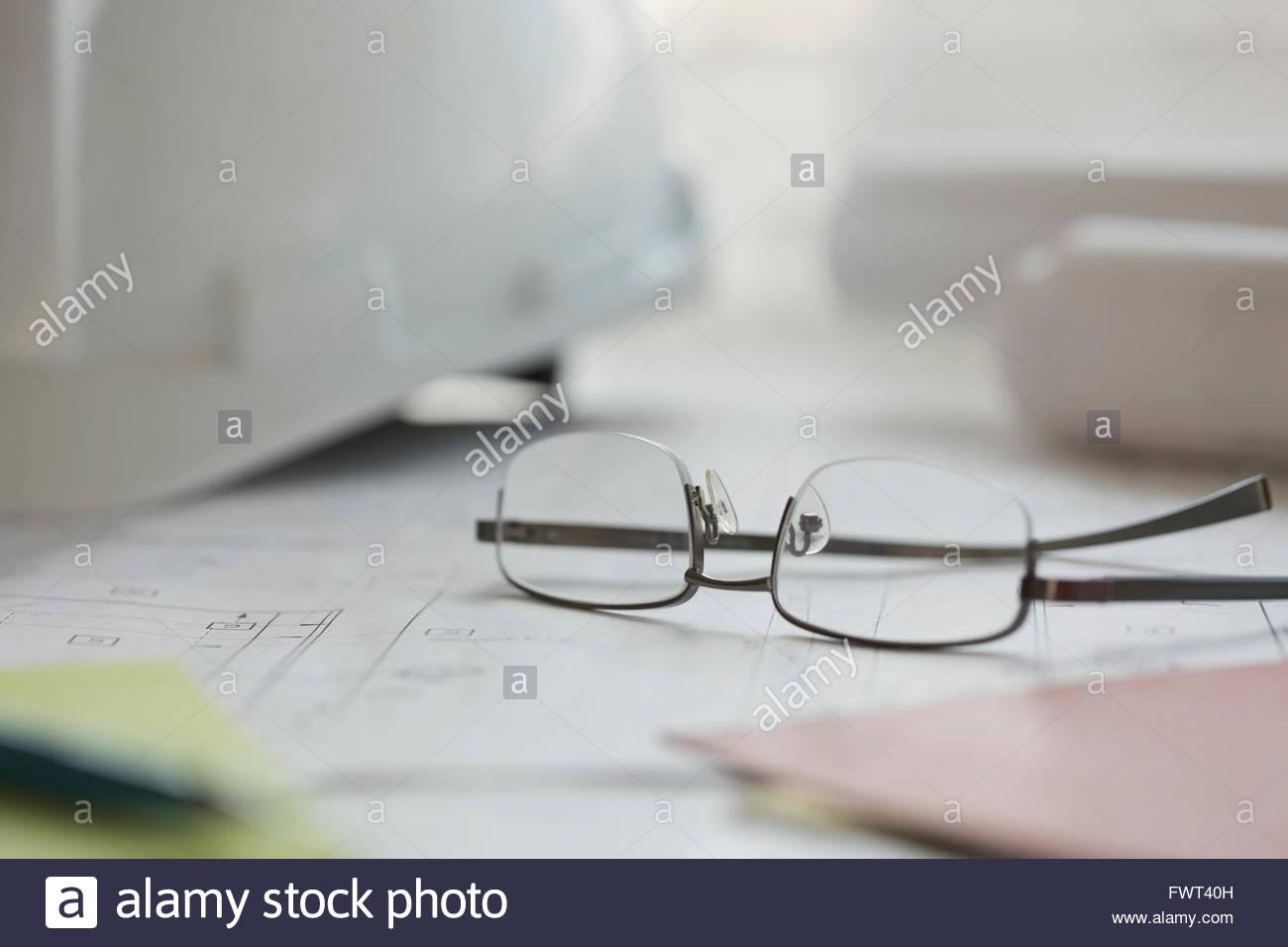 Eyeglasses and blueprint on office desk - Stock Image