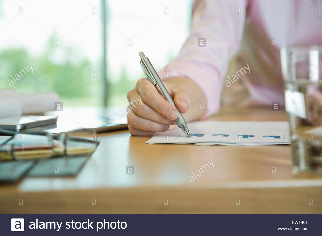 Cropped image of individual analyzing bar graph - Stock Image