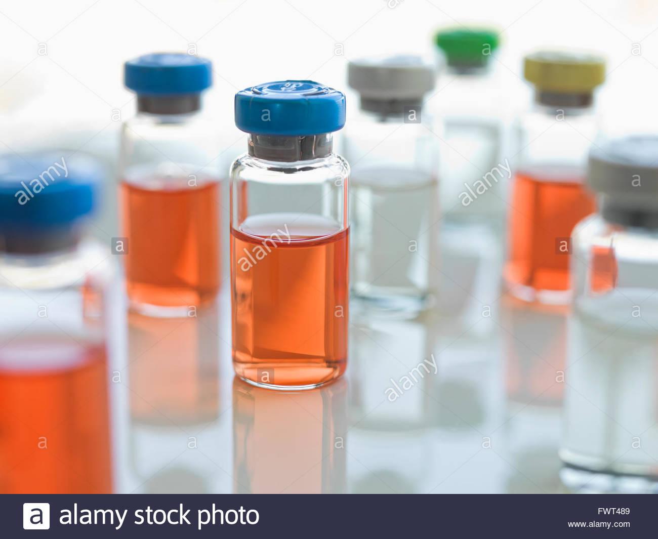 Medical sample bottles on table against white background - Stock Photo