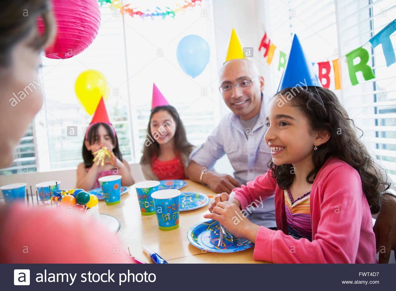 Birthday girl sitting at table with family - Stock Image