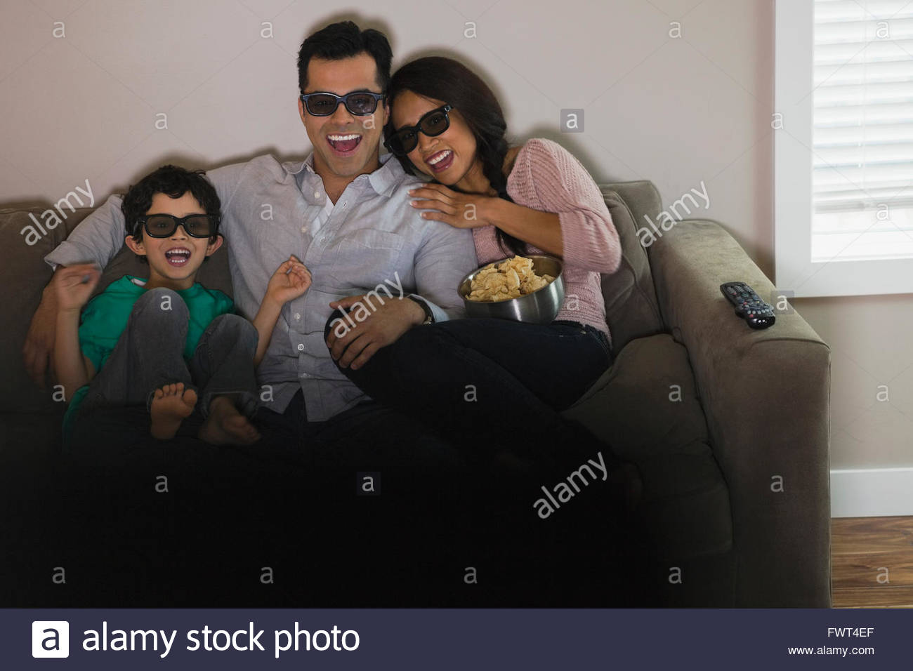 Family watching 3-D movie at home - Stock Image
