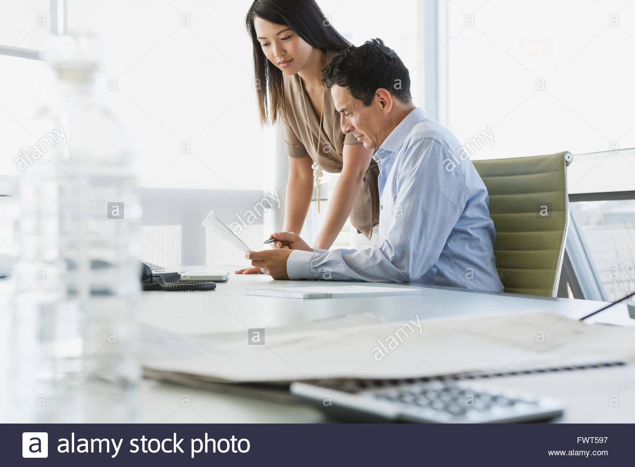 Business colleagues reviewing paperwork at office desk - Stock Image