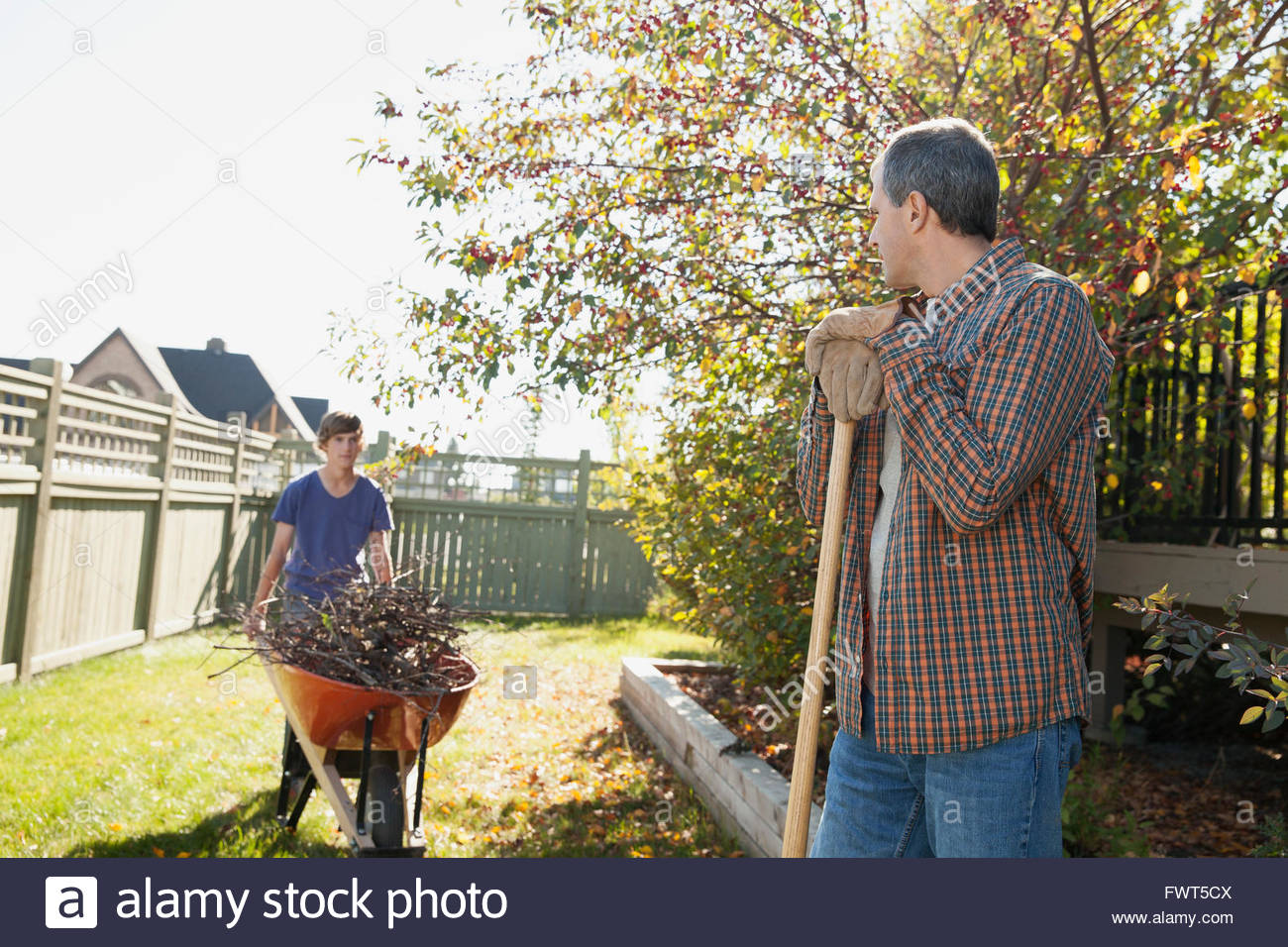 Father and son cleaning up yard together - Stock Image