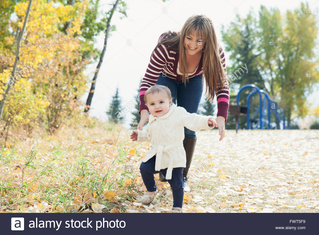 Mother helping baby girl to walk in park - Stock Image