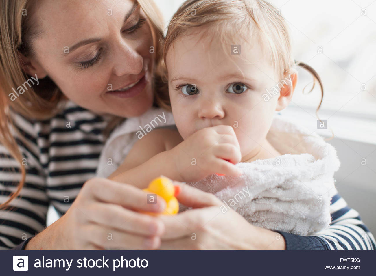 Mother holding baby girl wrapped in towel after bath - Stock Image