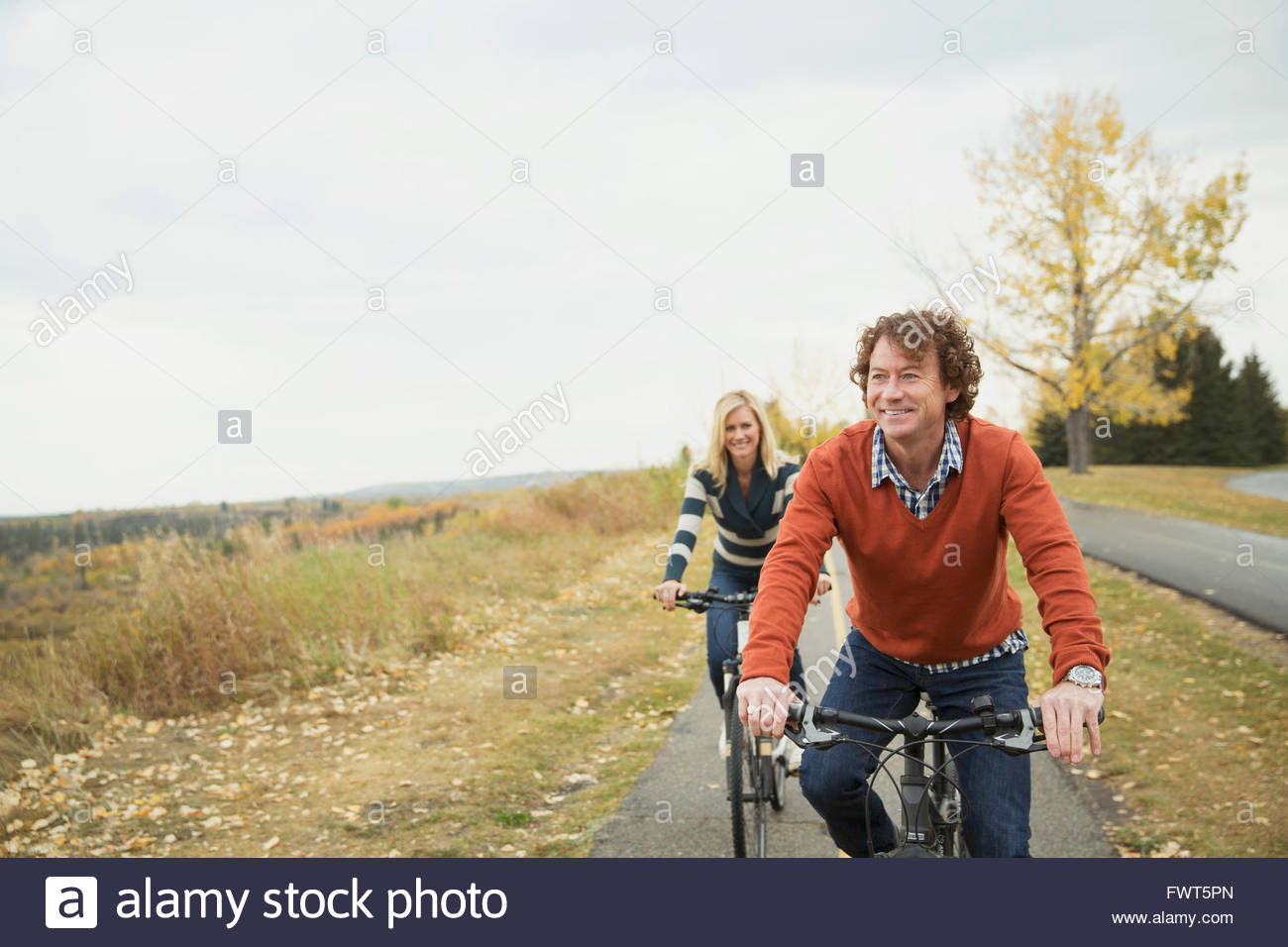 Mature couple cycling on pathway in park - Stock Image
