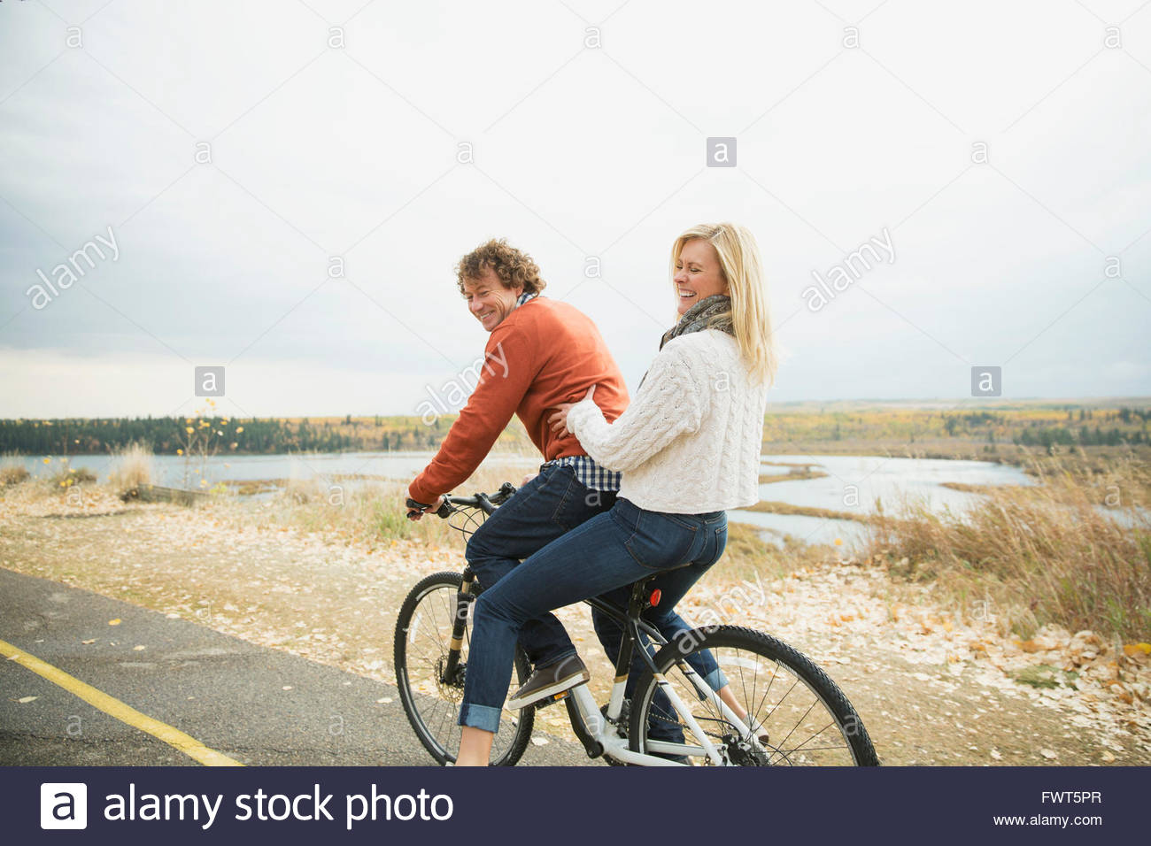 Couple riding bicycle together on roadway - Stock Image