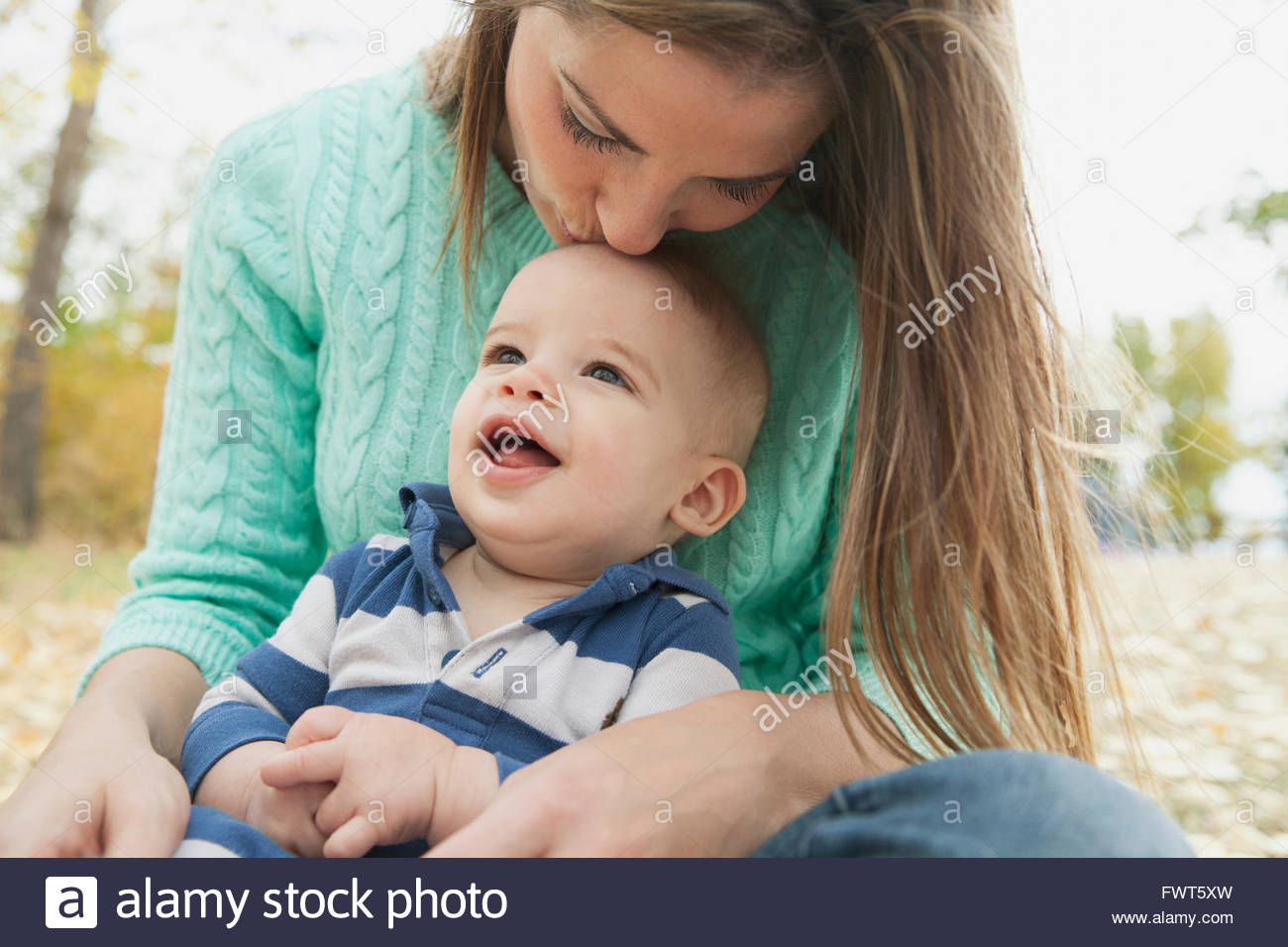 Mother kissing sons head at park - Stock Image